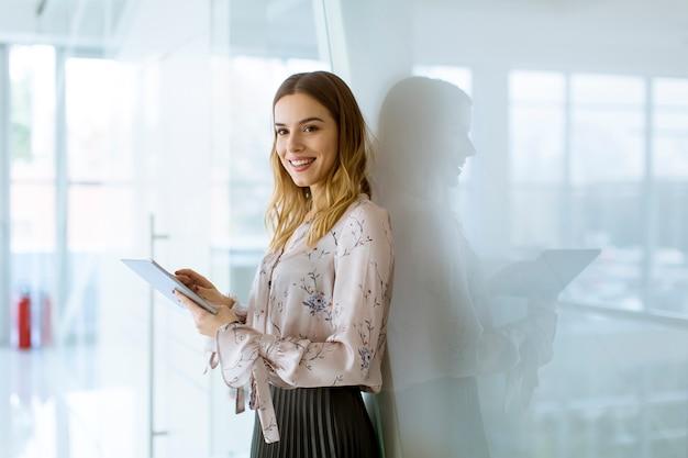 魅力的な女性実業家、オフィスに立っている間デジタルタブレットを使用して