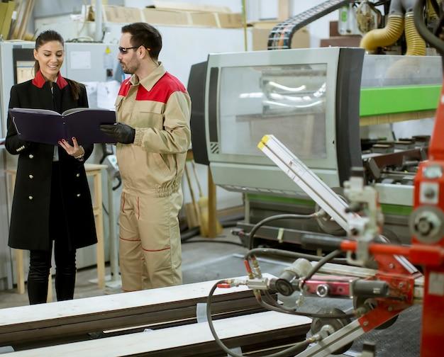 男性労働者と工場内のプロセスを制御する若い女性