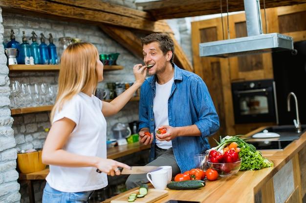 夕食を一緒に調理し、素朴なキッチンで楽しんで素敵な陽気なカップル