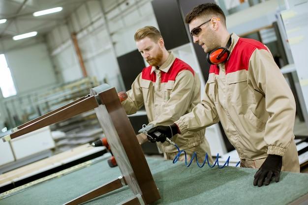 Двое молодых рабочих собирают мебель на фабрике
