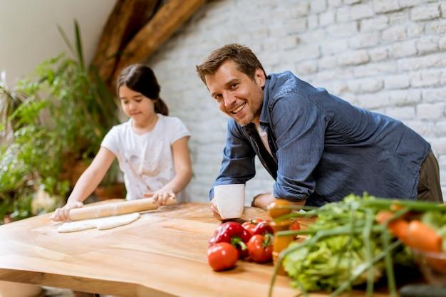 かわいい女の子と台所でパスタを準備する彼女のハンサムなお父さん