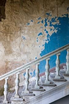 放棄された、台無しにされた建物の内部の古い階段