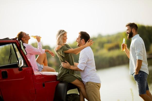 川でコンバーチブル車で楽しんでいる若い人たち