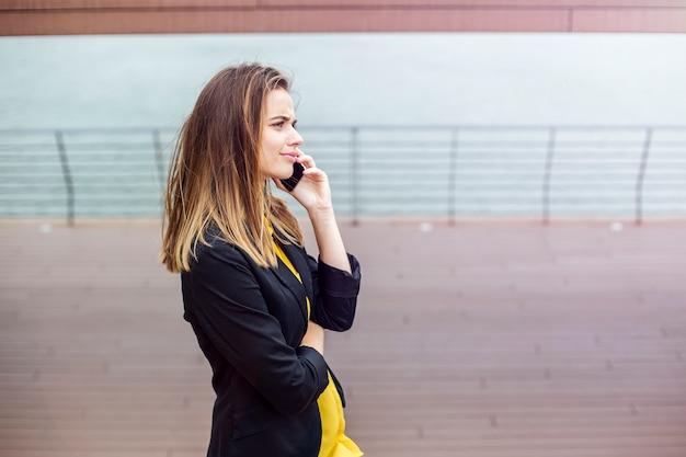 屋外の携帯電話で話しているかなり若い女性