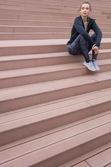 朝の実行中に階段で休んでいる間離れて見ているスポーツウェアとイヤホンの美しい若い女性
