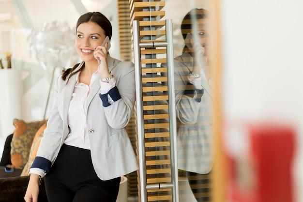 近代的なオフィスに携帯電話を持つかなり若い女性