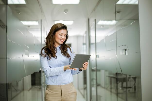 オフィスに立ちながらデジタルタブレットを使用して魅力的な実業家