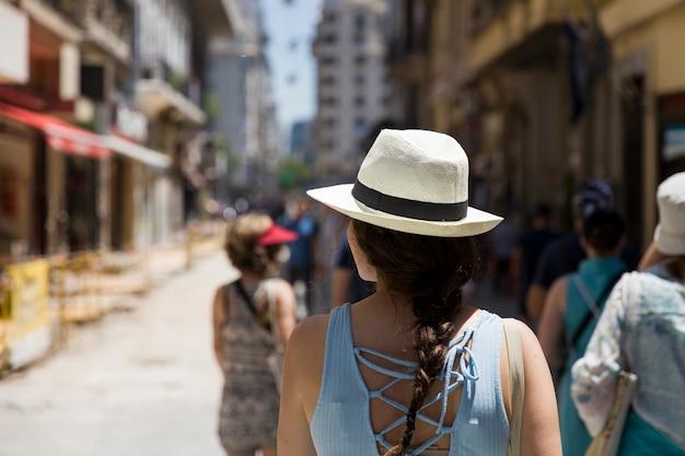 路上で帽子を持つかなり若い女性