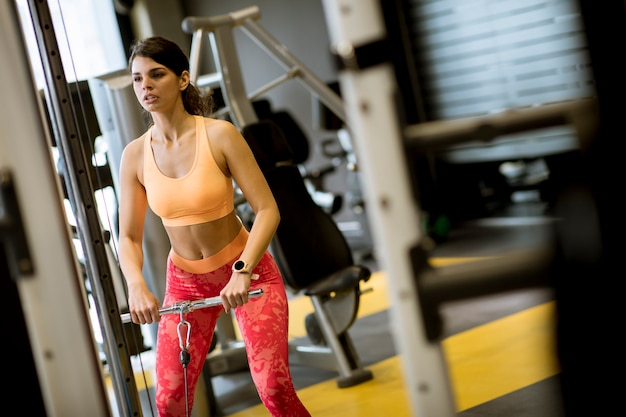 ジムで上腕二頭筋を行使する重みをプルするストレートバーケーブルを使用して女性