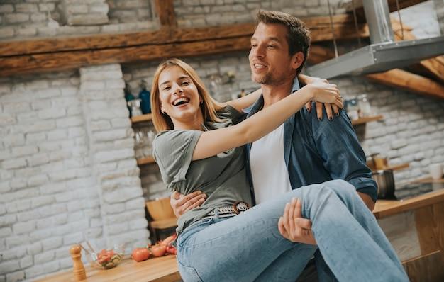 幸せなカップルは、モダンなキッチンでお互いを楽しむ男の手に女性を保持