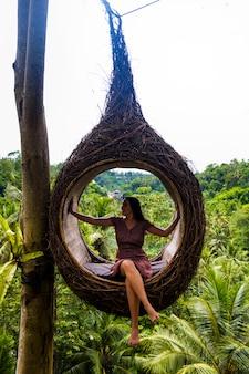 女性観光客はバリ島の木の上の大きな鳥の巣に座っています。