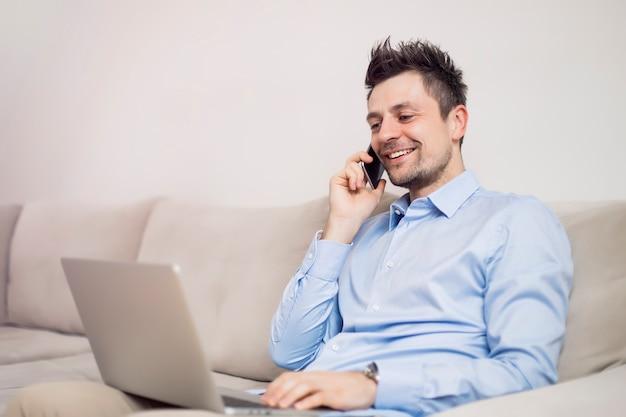 携帯電話を使用して、ラップトップに取り組んでいる青年実業家