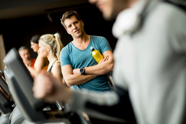 若い男がジムでスレッドミルに水のボトルを飲む