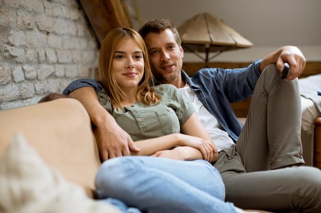 リラックスして自宅でテレビを見ている若いカップルの笑顔