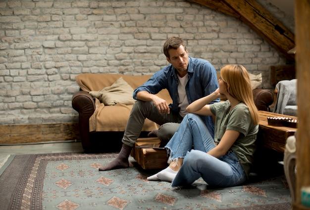 問題のある部屋に座っているカップル、彼は彼女が彼を慰めようとしている間、彼は怒っています