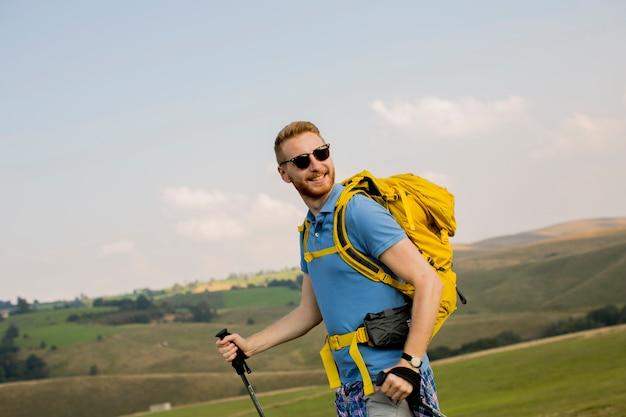 若い男は、晴れた日にハイキングを楽しんでいます