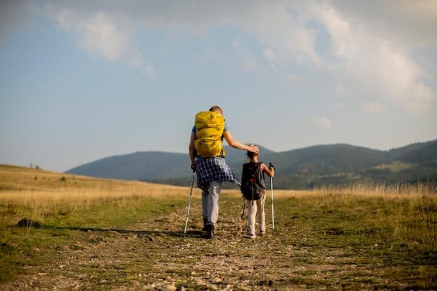 若い父と娘は晴れた日にハイキングを楽しむ