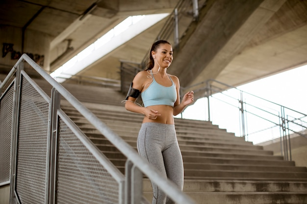 都市環境の屋外階段を一人で走っている若い女性