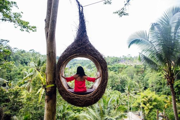 Женщина-турист сидит на большом птичьем гнезде на дереве на острове бали