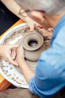 彼女のワークショップに座って陶器のホイールに取り組んでいるシニアの女性陶工