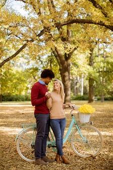 Многорасовая пара с велосипедом стоит в осеннем парке