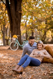 Молодая пара сидит на земле и с помощью мобильного телефона в осеннем парке