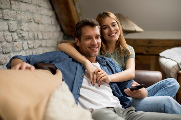 Улыбающаяся молодая пара отдыхает и смотрит телевизор дома