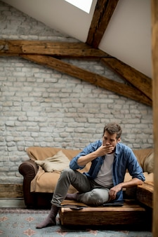 部屋に座っている若い男を強調