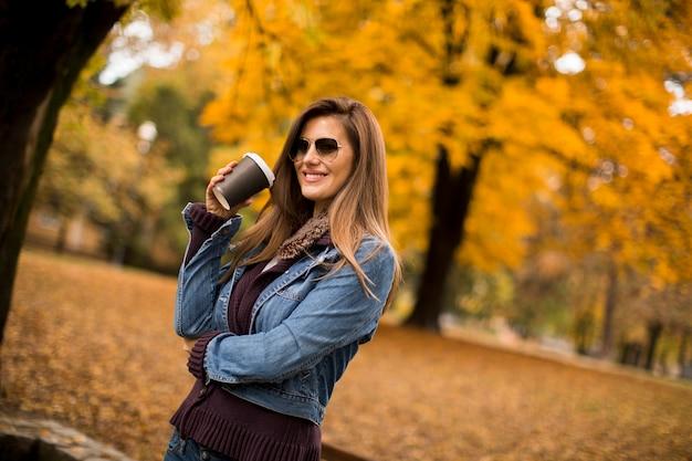秋の公園でコーヒーを飲む女性