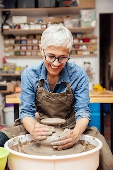 Старший женский гончар работает на гончарном круге, сидя в своей мастерской