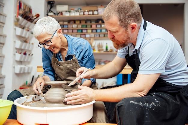 陶芸教室の先生とホイールに粘土を回転している年配の女性