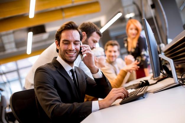 Старший бизнесвумен, работая вместе с молодыми бизнесменами в офисе