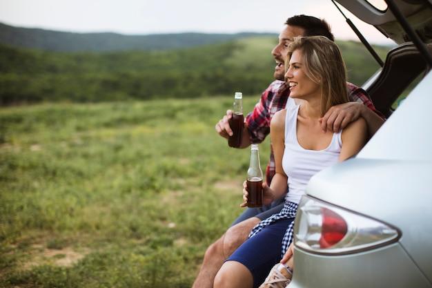 Влюбленная пара, сидя в машине транк во время поездки на природу