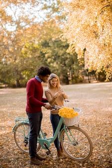 秋の公園に立って、携帯電話を使用して自転車と多民族のカップル