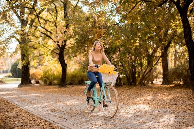 黄金の秋の公園で若い女性乗馬自転車
