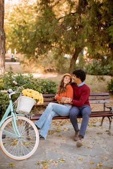 秋の都市公園のベンチに座っている多愛のカップル