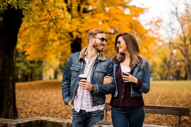 Молодая пара гуляет с кофе в осеннем парке