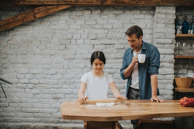 素朴なキッチンでパンを作る父と娘