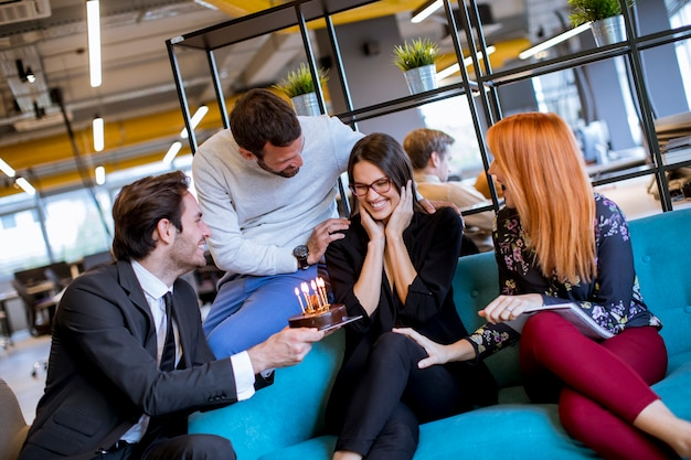ケーキと近代的なオフィスで若い女性の同僚の誕生日パーティー