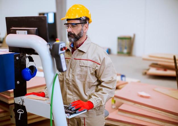 Старший человек, работающий на станках в современном заводском пульте управления