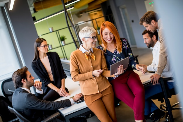 Счастливые деловые женщины, работающие вместе онлайн на цифровой планшет в офисе