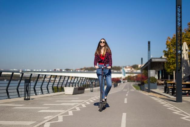 Милая молодая женщина на электрическом самокате на улице