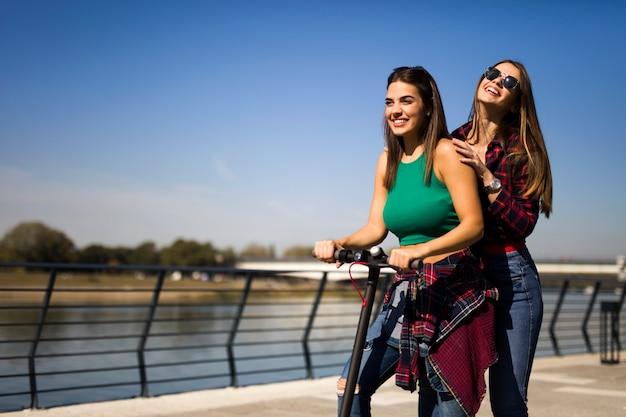 通りで電動スクーターに乗ってかなり若い女性の友人