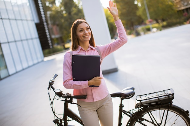 Молодая женщина с файлами в руках стоял открытый рядом с электрическим велосипедом