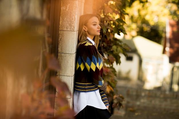Молодая женщина, стоящая на улице в солнечный осенний день