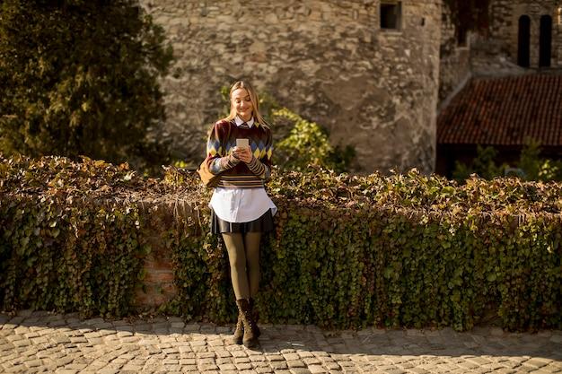 秋の日に路上で携帯電話で立っているかなり若い女性