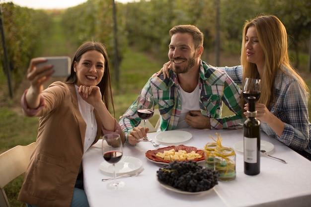 テーブルのそばに座って、ブドウ園で赤ワインを飲む若者のグループ