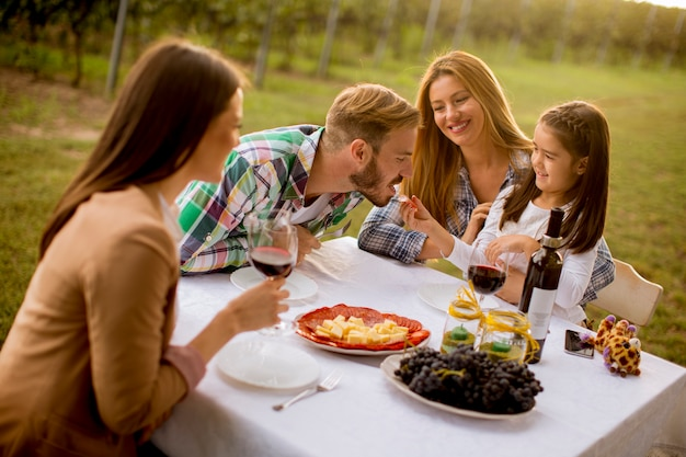 Молодые люди наслаждаются ужином и дегустацией вин на винограднике