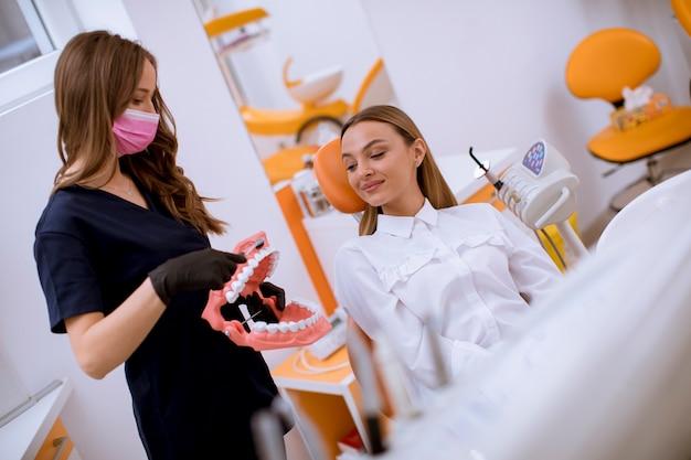 Молодой женский дантист объясняя женской терпеливой процедуре чистки зуба с зубной щеткой на модели