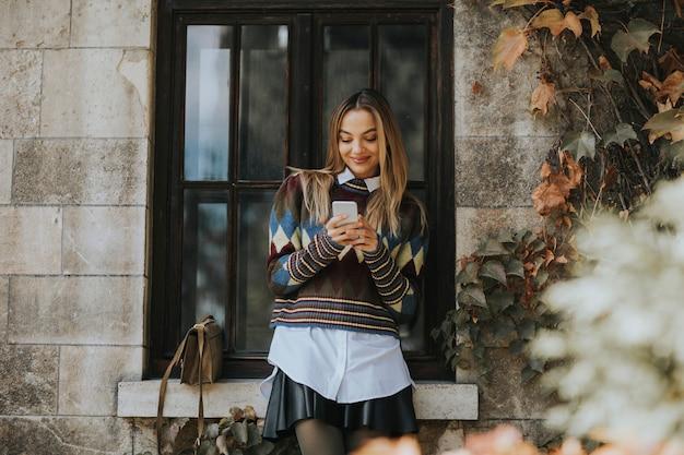 Довольно молодая женщина, стоя с мобильного телефона на улице в осенний день